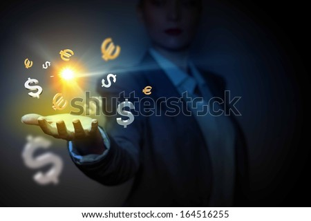 Currency symbols on human hand. Money making and wealth - stock photo