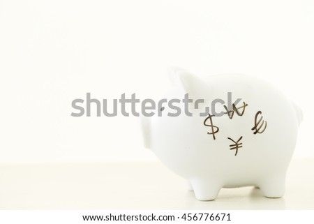 Currency symbols written on piggy bank