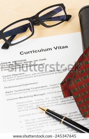 Curriculum vitae or CV with pen, glasses, organizer, and neck tie; concept job applying - stock photo