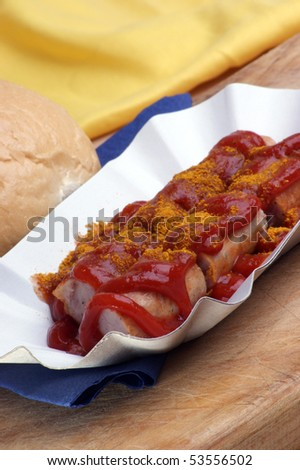 curried sausage with ketchup on paper plate - stock photo