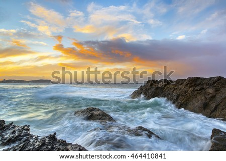 Currumbin Rock Gold Coast, stormy sunset with ocean tide rushing over the rocks.