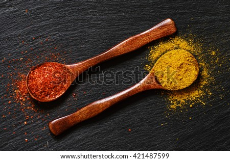 Curry and chili pepper spices, wooden spoons, black stone background, food background, top view - stock photo