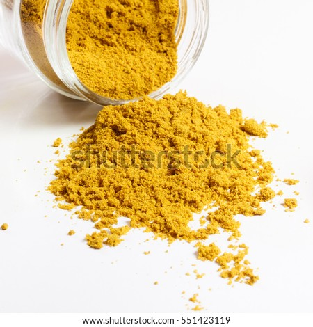 Curry in glass jar. Heap. Isolated on white.
