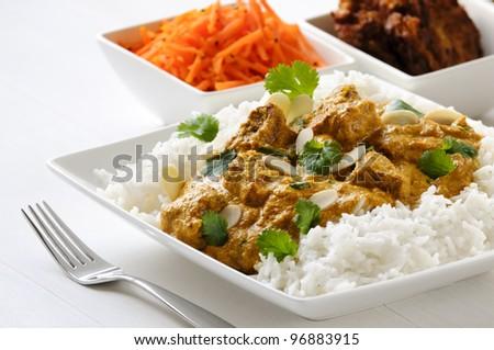 Curry meal - lamb pasanda with rice, bhaji and carrot salad behind. - stock photo