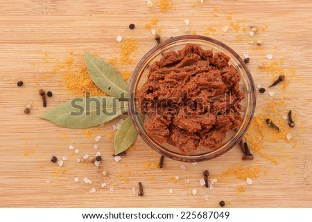 Curry paste in glass bowl with various spices on wooden background - stock photo