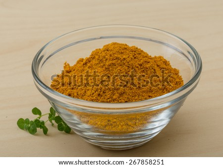 Curry powder heap in the glass bowl - stock photo