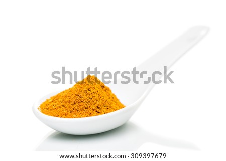 Curry powder spice on a white porcelain spoon - stock photo
