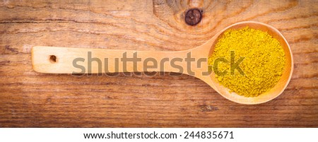 curry powder spices on spoons,on wooden background - stock photo