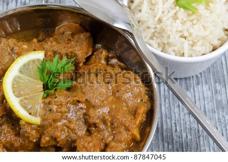 Curry & Rice - Indian curry garnished with lemon with rice on slate. - stock photo
