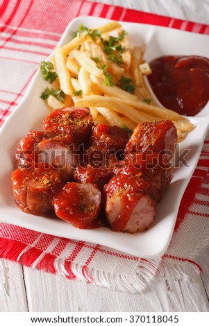 Currywurst and fries close-up on a plate on the table. vertical - stock photo