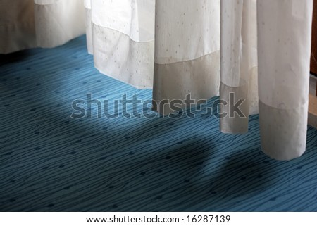 Curtain low hanging above a carpet covering - stock photo