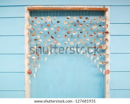 curtain shells hanging on the blue door. - stock photo