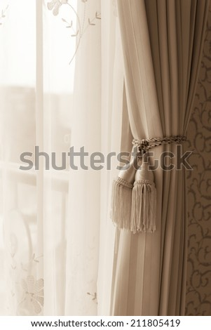 Curtain with curtain tieback at window, selective focus.  Processed with vintage style. - stock photo