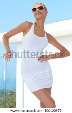 Curvaceous woman in white miniskirt and sunglasses posing on a sunny summer patio - stock photo