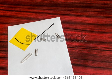 Curve graph printed on a sheet of paper and yellow note with spreaded paper clips - stock photo