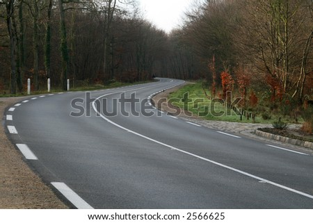 Curve in a road in autumn - stock photo