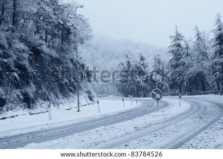 curve made ??dangerous by snow - stock photo