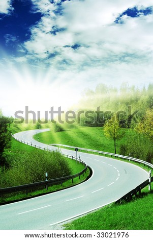 curve of a highway with bright sun - stock photo