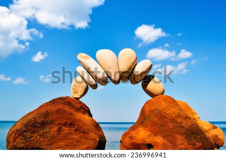 Curve of pebbles between of the red stones on the seashore - stock photo