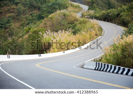 Curve of the road on mountain in country, with grass flower on both sides. - stock photo