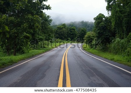 Curve road on mountain whit green trees background and misty sky in early morning.