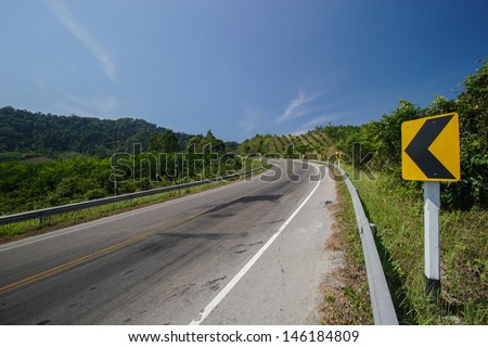Curve road sign on down hill  - stock photo