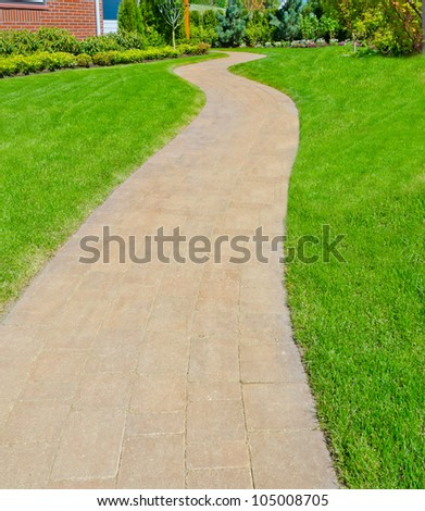 Curved and paved path with nicely trimmed grass aside - stock photo