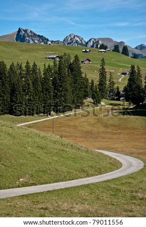 curved asphalt road on countryside on sunny day, juan pass range, swiss - stock photo