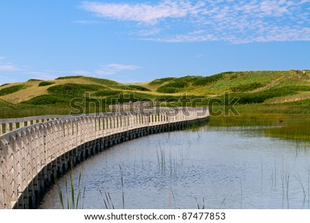 Curved boardwalk across water to sand dunes and the sea in the National Park in Prince Edward Island, Canada - stock photo