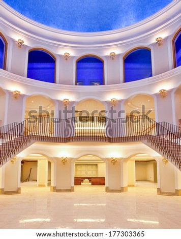 Curved building interior with symmetrical arches on three floors and a dual staircase under a blue painted ceiling illuminated with up-lighters - stock photo