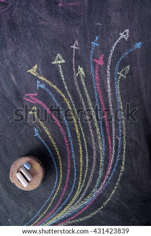 Curved colored arrows drawn with chalk on blackboard - stock photo