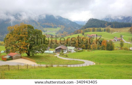 Curved country road winding between green meadows and trees leading to a farmhouse on a beautiful autumn hillside ~ Autumn landscape of countryside in Ramsau Bavaria Germany ( vivid version) - stock photo