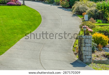Curved driveway to the building, house with nicely landscaped and trimmed sides. - stock photo