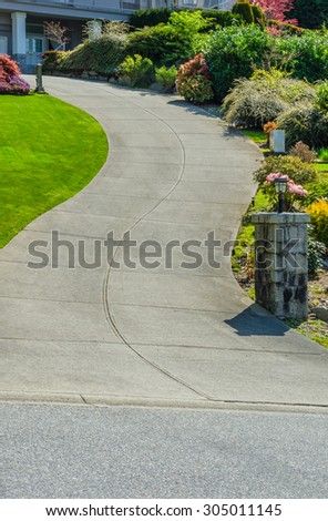 Curved driveway to the building, house with nicely landscaped sides. Vertical. - stock photo