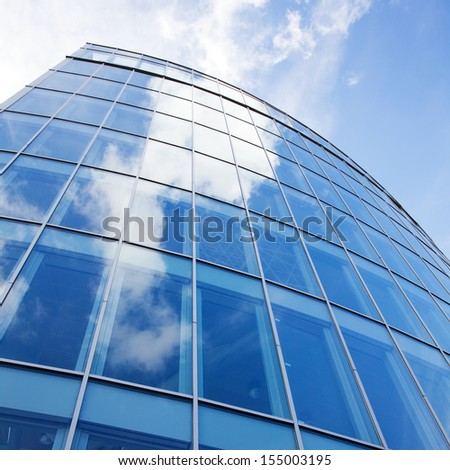 curved facade of modern glass blue office and sky with clouds reflected - stock photo