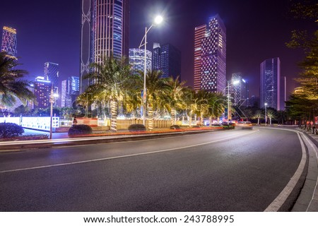 curved light trails on the city road in guangzhou central business district with modern buildings at night  - stock photo