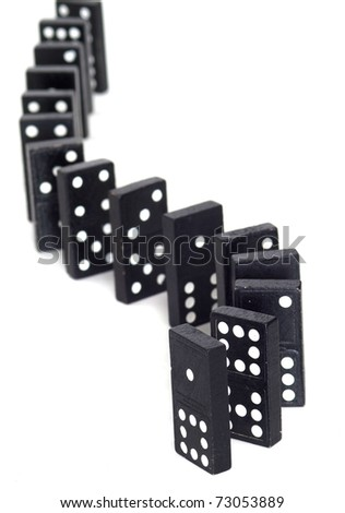 Curved line of dominos waiting to be toppled - stock photo