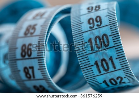 Curved measuring tape. Measuring tape of the tailor. Closeup view of blue measuring tape. Tape measure as symbol of healthy lifestyles. - stock photo