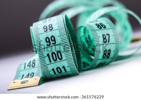 Curved measuring tape. Measuring tape of the tailor. Closeup view of green measuring tape. Tape measure as symbol of healthy lifestyles. - stock photo