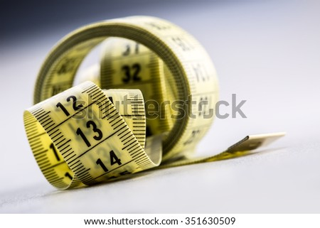 Curved measuring tape. Measuring tape of the tailor. Closeup view of yellow measuring tape - stock photo