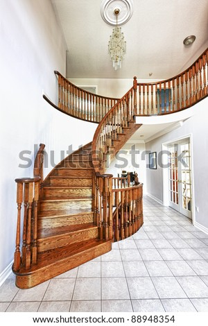 Curved oak staircase in luxury home entrance hall - stock photo