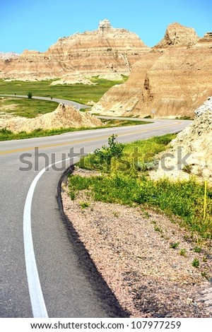 Curved Road in Badlands. Badlands National Park Curved Road Vertical Photography. U.S. National Parks Photo Collection. - stock photo