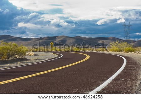Curved road in the desert with dramatic sky - stock photo