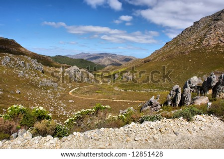 Curved road in valley between mountains. Shot in Hottentots-Holland Mountains nature reserve, near Grabouw, Western Cape, South Africa. - stock photo