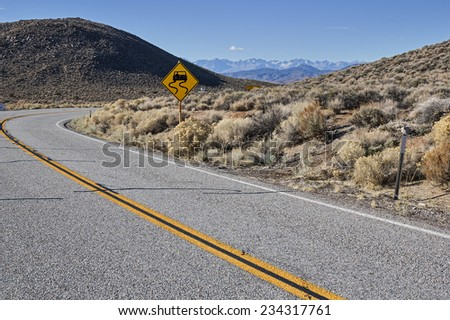curved road with slippery road sign and distant mountains - stock photo