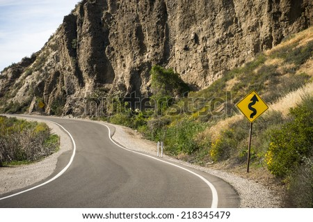 Curved road with Windy road ahead signpost - stock photo