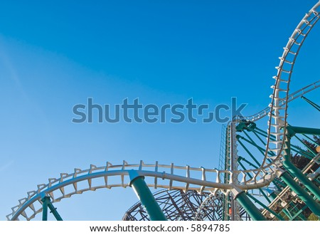 curved rollercoaster tracks at the clear blue sky - stock photo