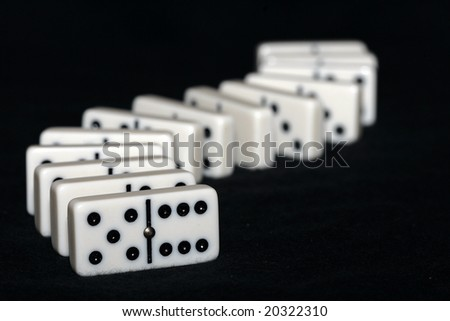 Curved row of arrangned dominoes - stock photo
