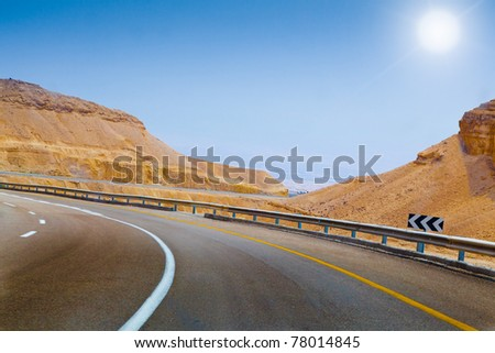 curved sandy road blue sky and sun on the way in Israel - stock photo