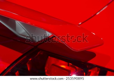 Curved spoiler of aggressive powerful sport red car - detail - stock photo